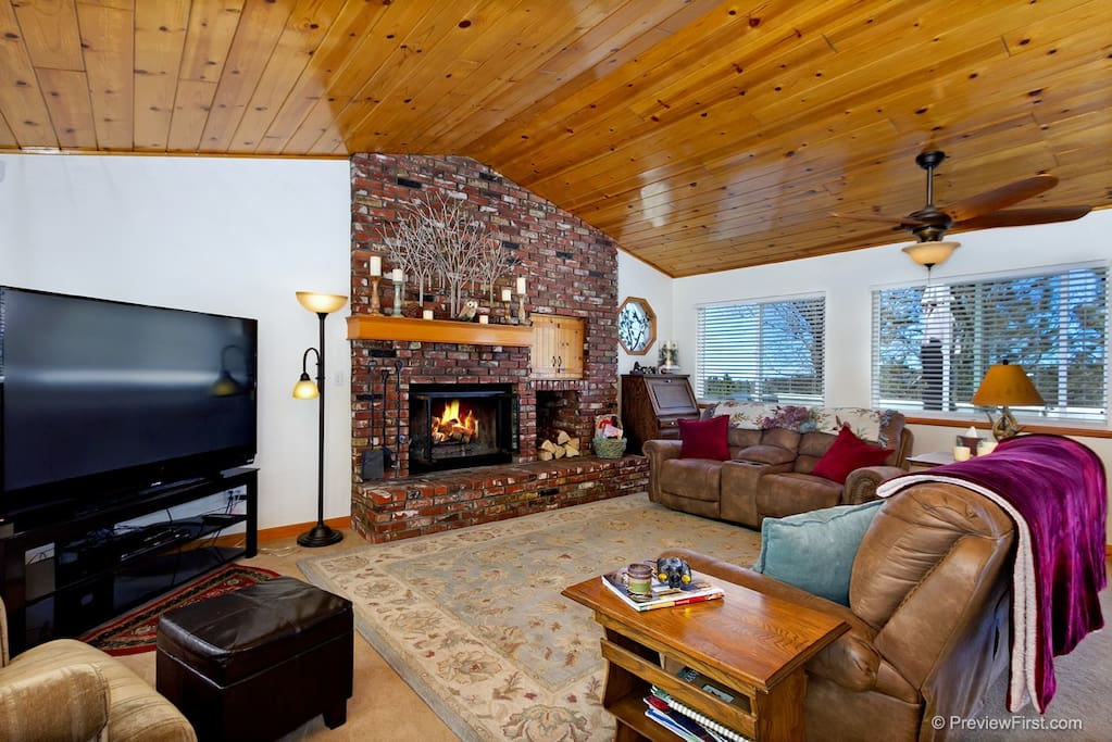 Living room with warm fireplace and large screen tv.