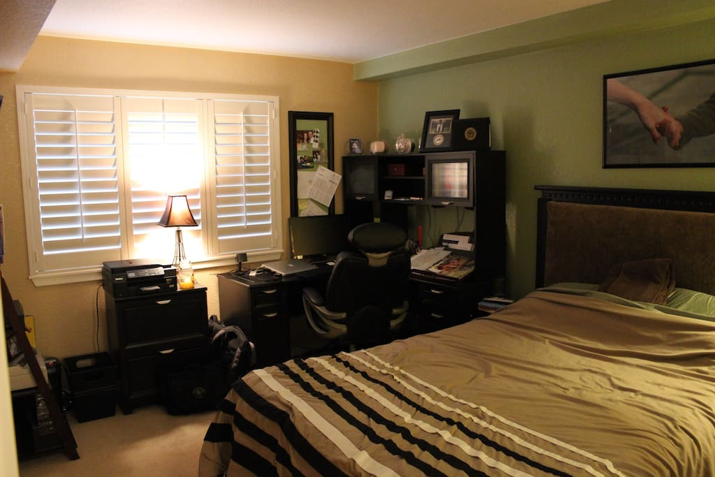 Private Room with queen size bed, desk, and wall  mounted TV.
