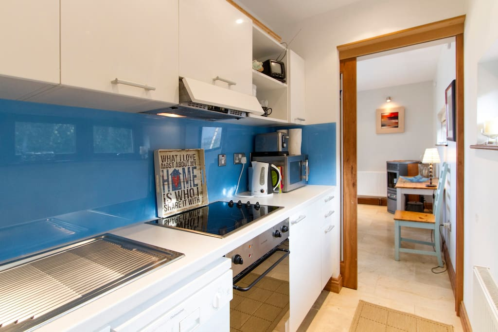 Compact Galley kitchen with bespoke splash back , dishwasher, electric hob , oven , fridge, toaster , kettle and microwave .