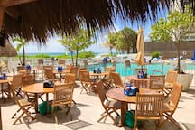 Next to beach and pool outdoor tiki restaurant dining