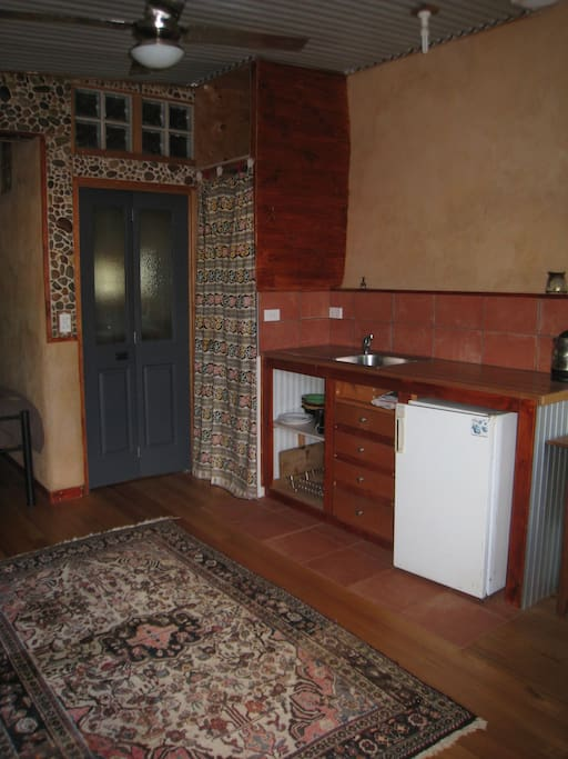 Kitchenette with bathroom through rear folding door.