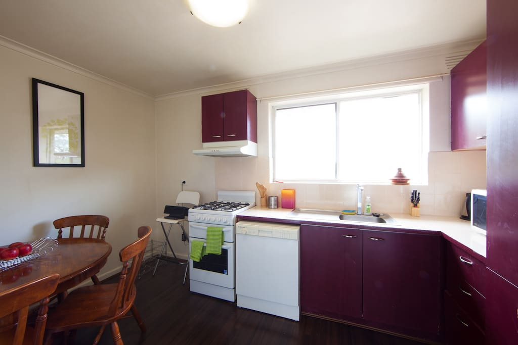 Kitchen, with a dining table, microwave, gas stove and oven.