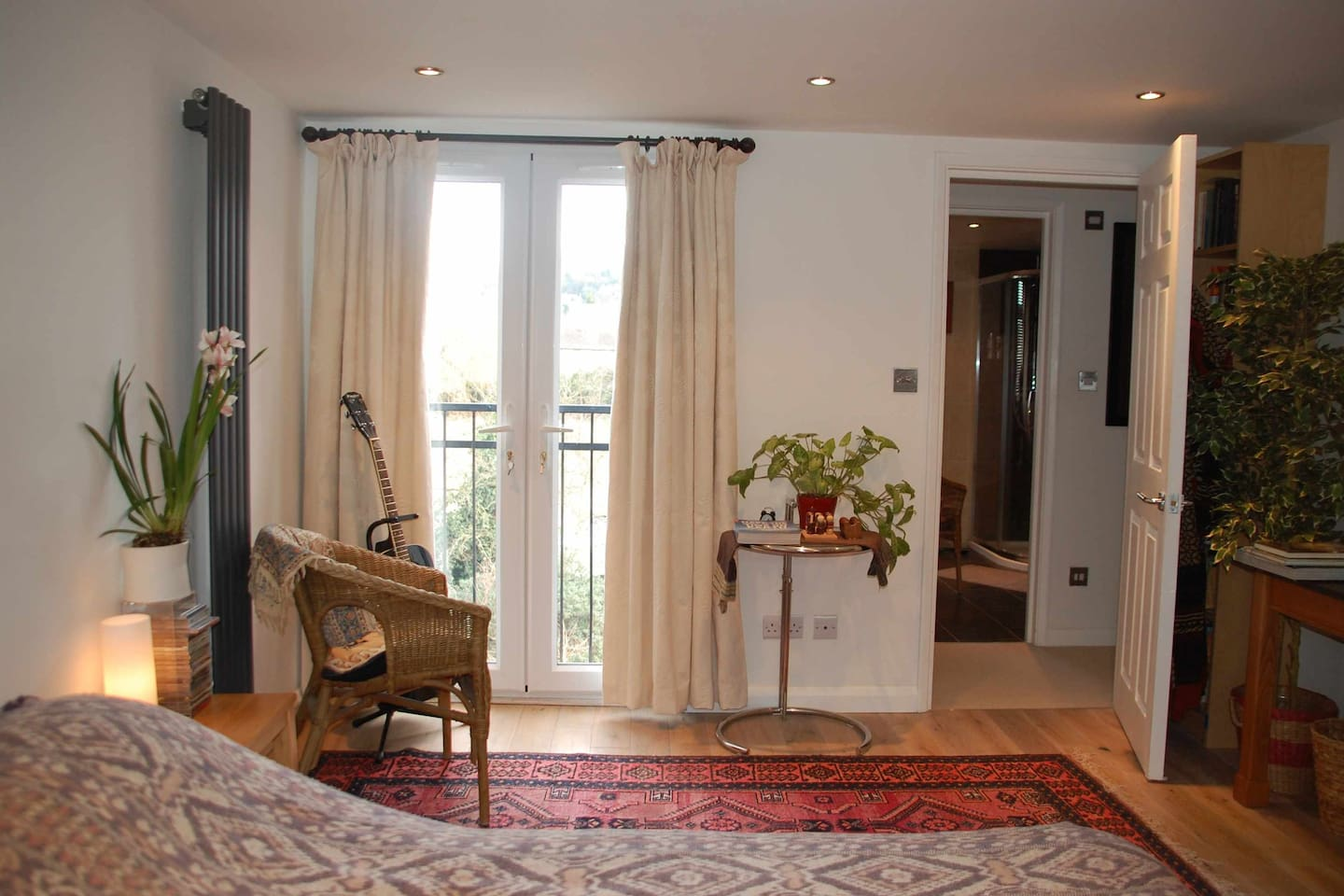 View over the bed to the French doors which open to the Juliette  balcony with views to the Hill. Your very own en-suite bathroom to the right.