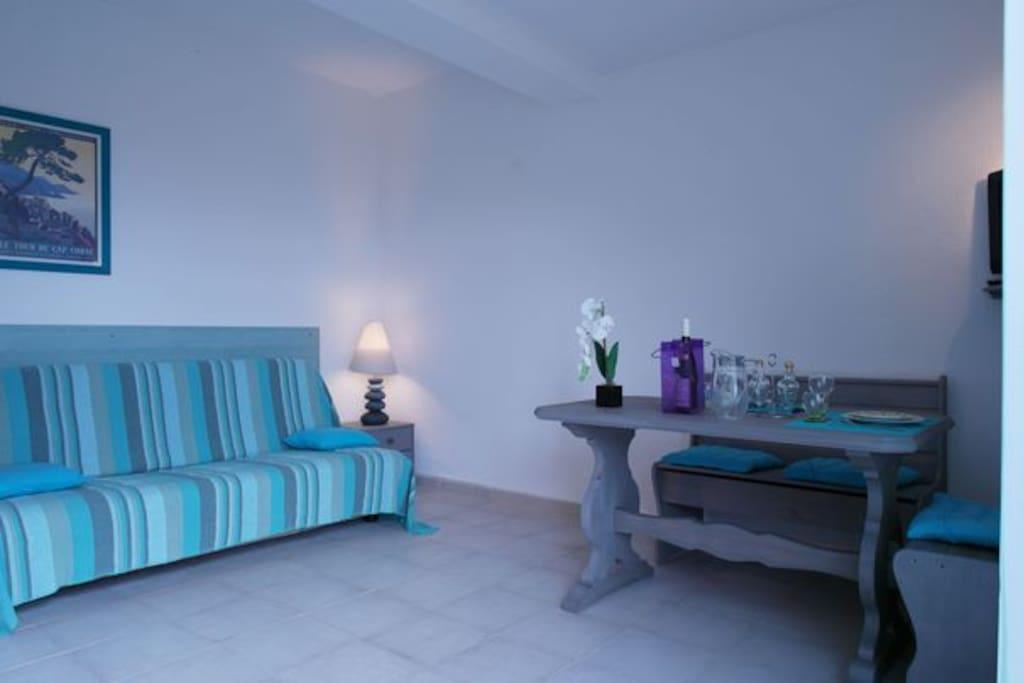 Un vaste séjour avec un coin repas, un canapé convertible en couchage de 140 cms bulex 17 cms vue sur la terrasse