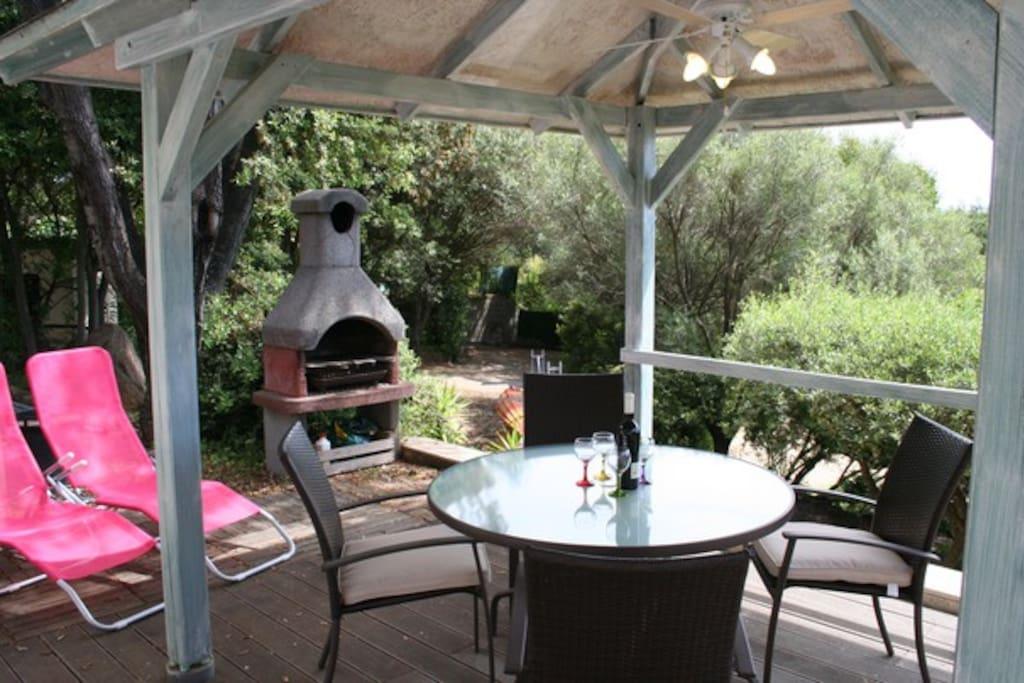Niché dans un écrin de verdure et vue mer, une jolie table ronde en verre et 4 fauteuils confortables, 2 transats et un BBQ à bois ou charbon