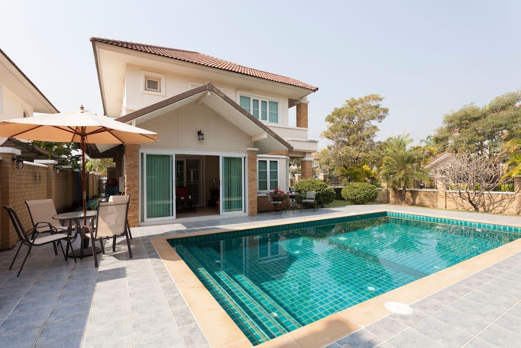 Corner view of swimming pool with umbrella table