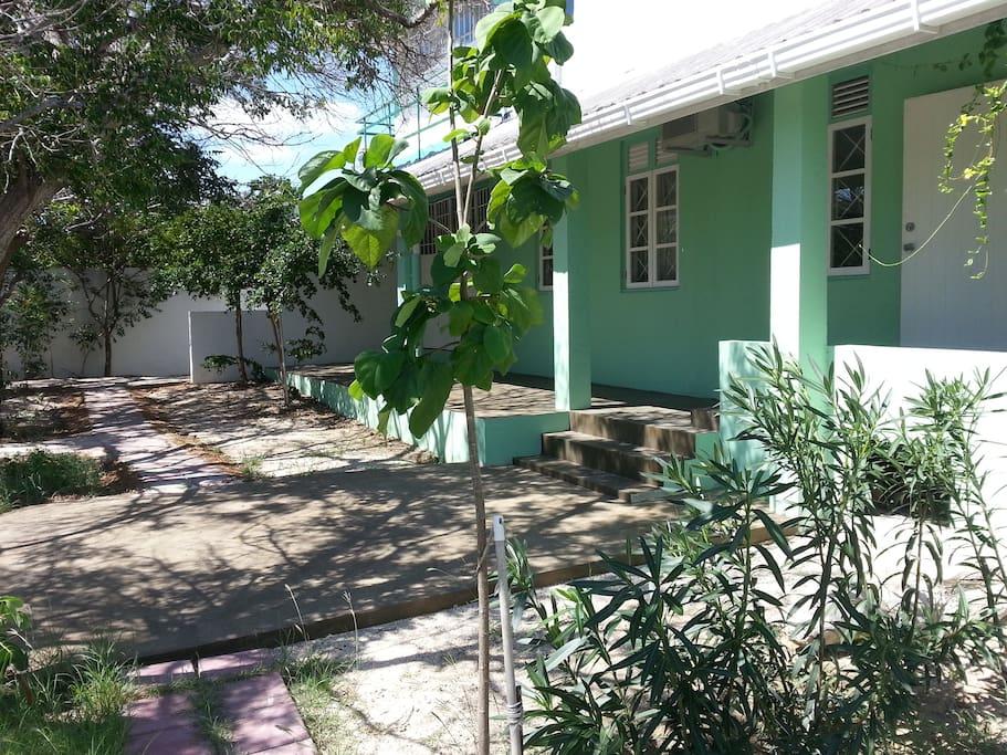 Garden view. From right to left: Entrance, kitchen window, Bedroom windows, Folding door living room.