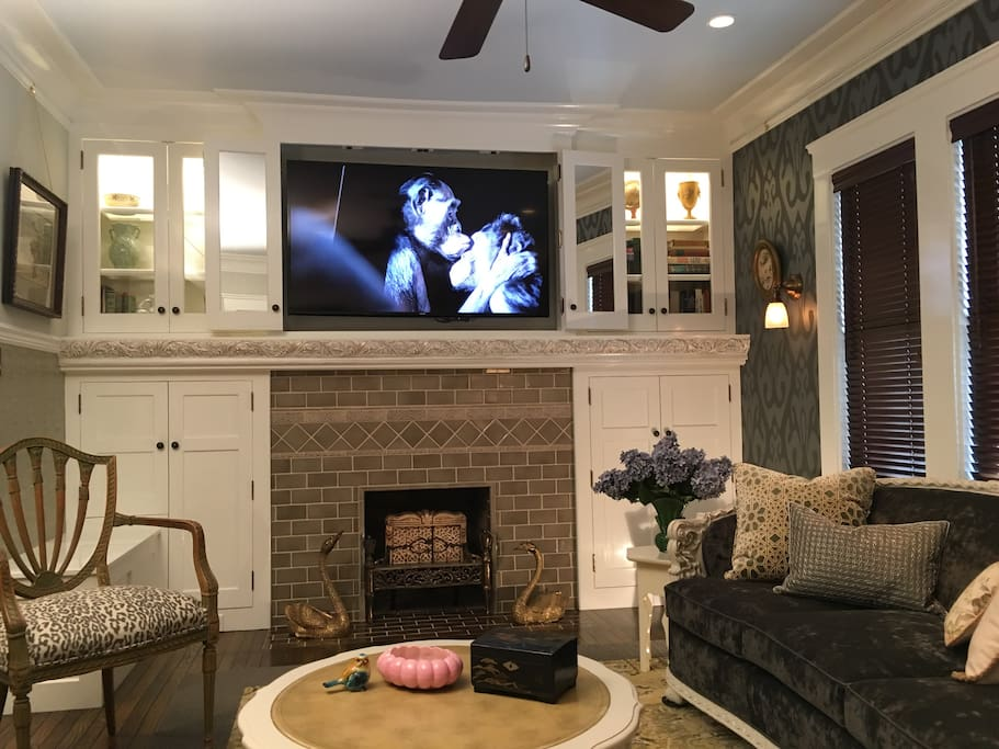 """60"""" Samsung Smart TV. Tiled fireplace surround, built-in, lighted cabinets and bookcases."""