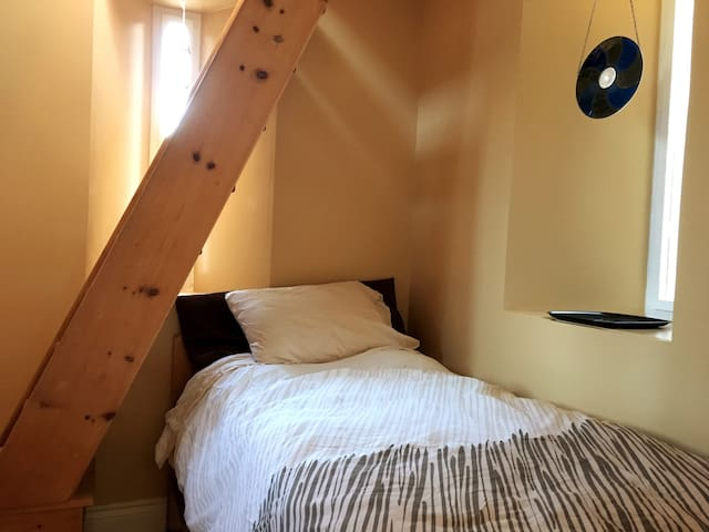 Recommended for adults: Cozy bedroom with single bed built into the bell tower with arrow-slit windows . Ladder stairs require extra attention to safety.