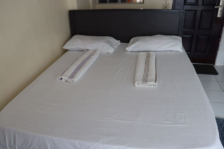 King size bed spread with white soft linen.Soft pillows available. Soft white towels provided.
