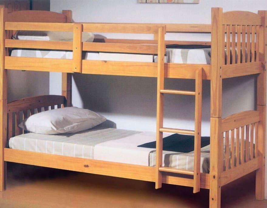 Two bunk beds in a cozy room with parquet flooring