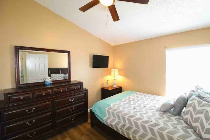 Bedroom #3 located on the second floor with a 24in wall mounted flat screen smart TV, featuring a QUEEN bed laying out on premium vinyl laminate floor finished with ceiling light/fan