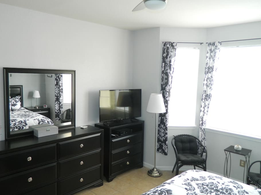 Master bedroom with dresser and 40 inch smart TV