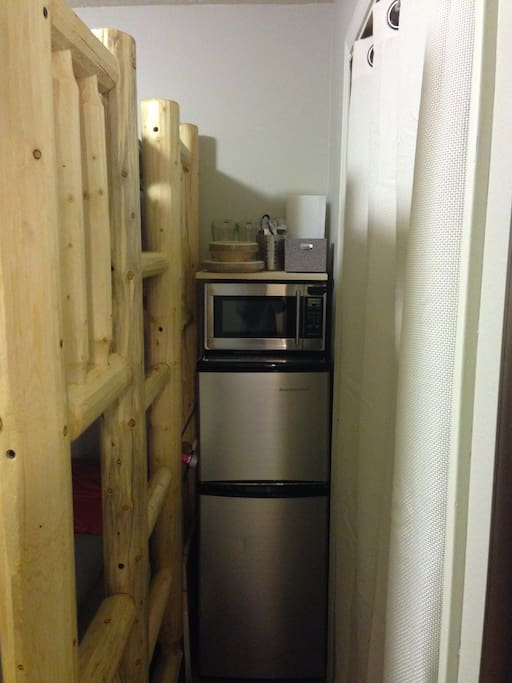 Fridge, Microwave, and basic utensils are included between the bunkbed and closet.