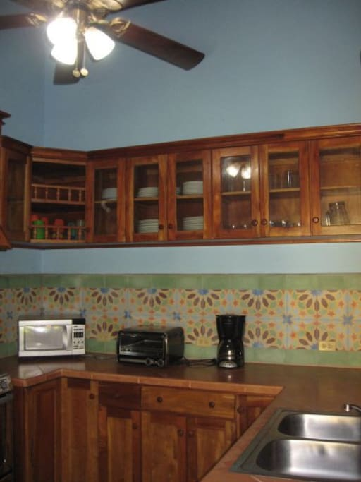 Kitchen prep area with all plates, glasses microwave, coffee maker and toaster oven.