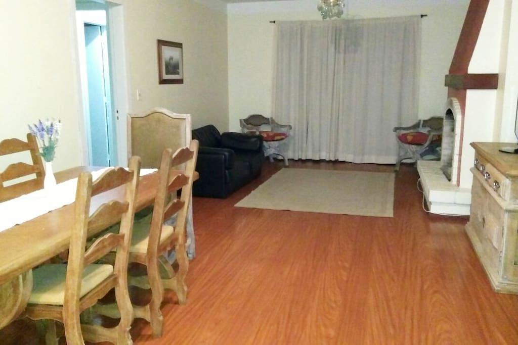 Sala de jantar, sala de estar com lareira e sacada.