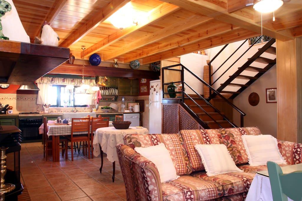 Cuarto de estar con cocina al fondo y escalera de subida a la buhardilla