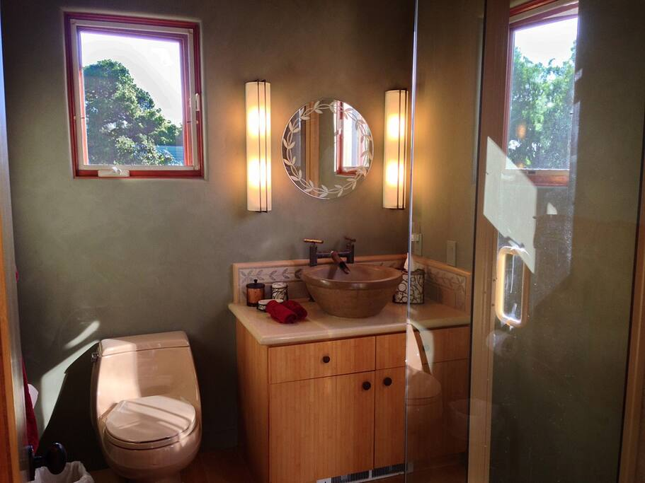 Bathroom features concrete vessel sink, custom copper faucet, glass enclosed showed and floor heater