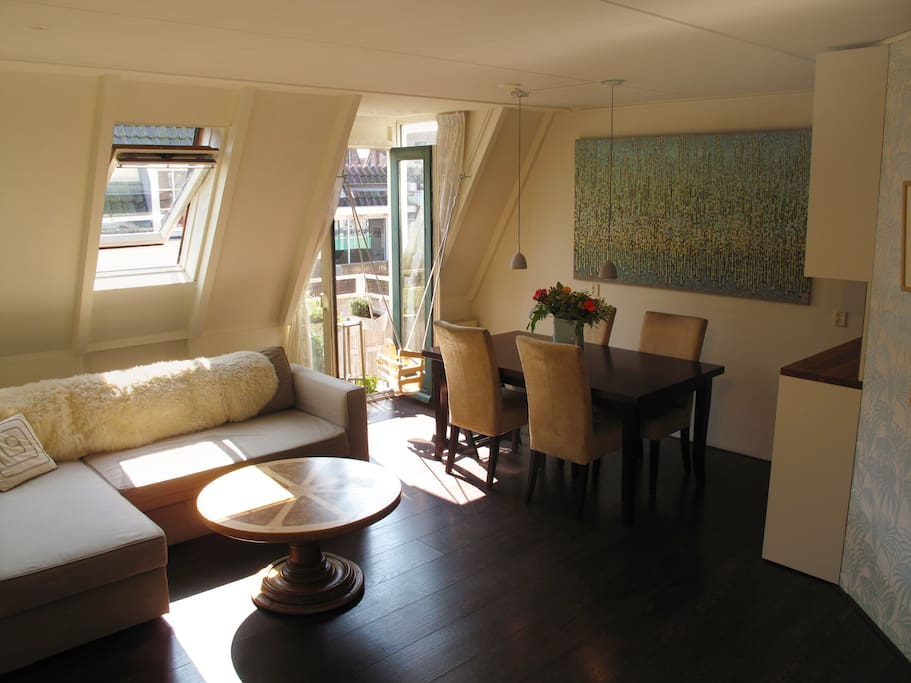 Beautiful 60 sqm apartment in the Jordaan - living room and dining area, with angled windows and French balcony.