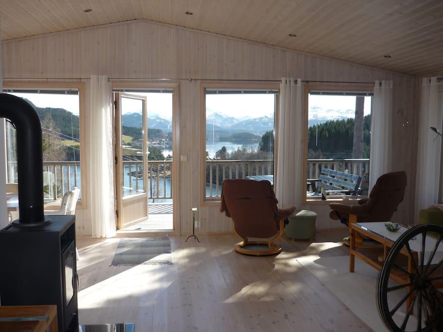 Stua med 6 store vinduer mot sjøen og verandadør. Vedovn og sittegruppe.