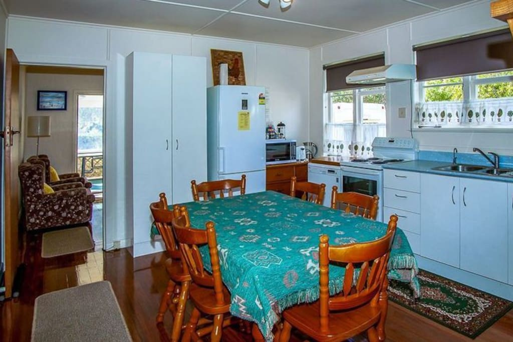 Open plan kitchen and dining area - Nellies Beach Cottage, Matapouri Bay Holiday Home