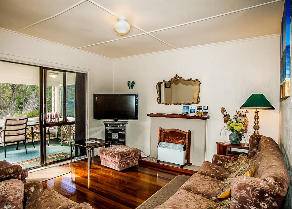 Lounge leading to the deck and garden - Nellies Beach Cottage, Matapouri Bay Holiday Home