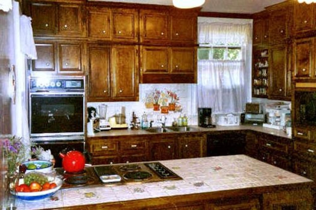 Kitchen has modern appliances and mounted tv