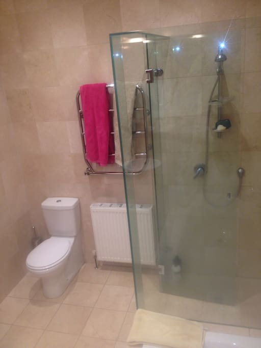 Walk in shower, with flexible hose and shower head, heated towel rail, hydronic heating, marble tiles