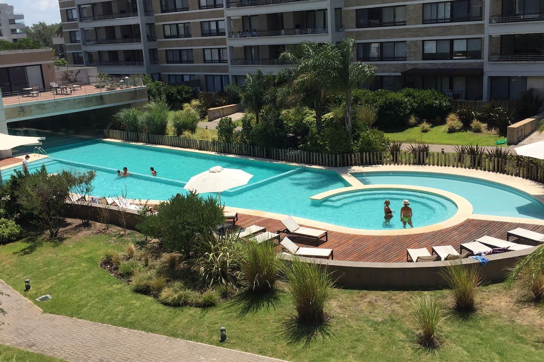Enorme pileta con 3 zonas para niños pequeños, para nadar y de recreación con amplio solarium y reposeras para todos.