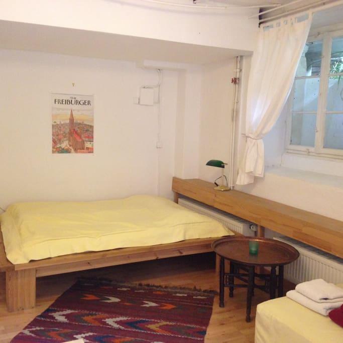 Das Bett ist 140 cm breit und für 2 Personen geeignet. Das Fenster geht in einen Lichschacht.