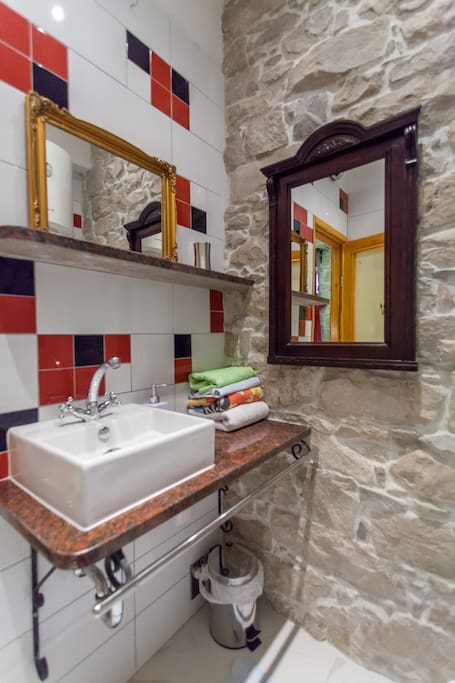 Notice the fanciful mixed match tile, large wash basin, generous mirrors...