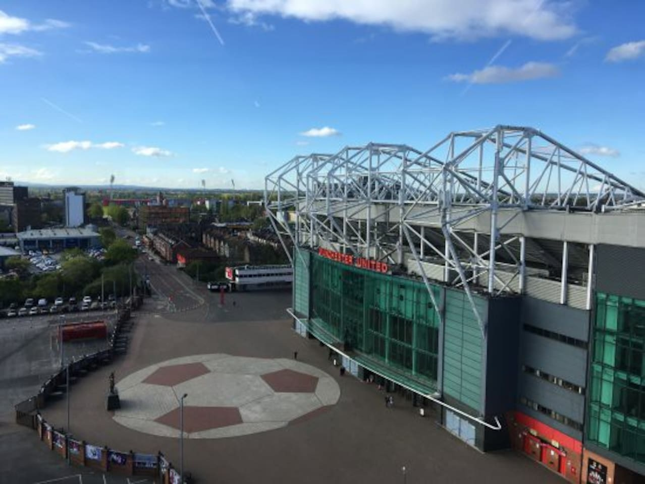 View up Sir Matt Busby Way with Manchester United stadium in foreground and Old Trafford Bunkhouse in the background