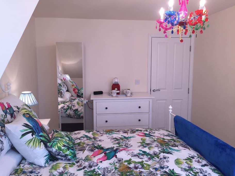Main bedroom with coloured chandelier, Happy Friday bedding  & white furniture