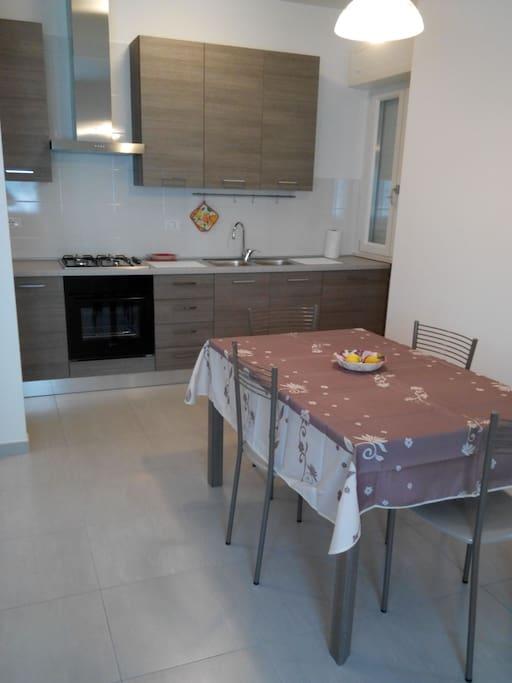 Angolo cottura con fornelli, forno frigo, lavandino con tavolo e sedie