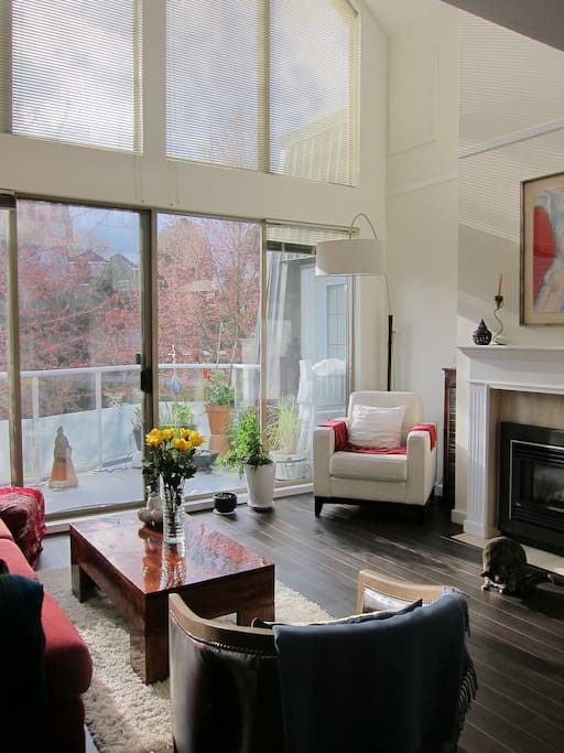 Spacious living room with fireplace and corner reading nook, overlooks front deck.