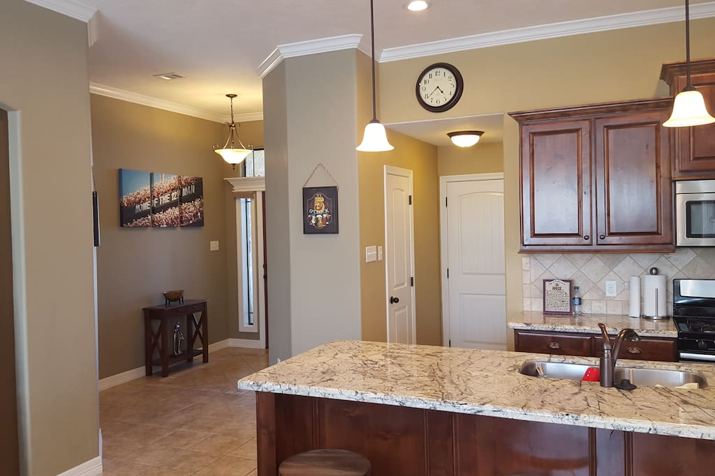 Open concept kitchen, fully equipped with appliances, dishware, and cookware. Large kitchen island for cooking and entertaining needs.