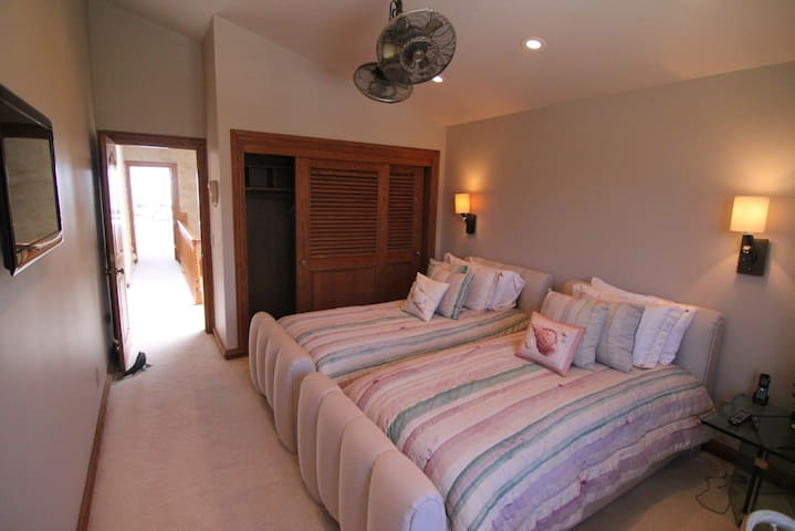 Guest Bedroom 1 has two long twin beds, a flat screen television, a walk-in closet, a double ceiling fan