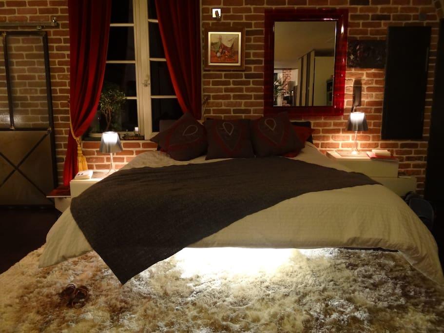 le coin nuit belle grande fenêtre au calme donnant sur une cour intérieure et vue sur les toits et le jardin  du musée du nouveau monde
