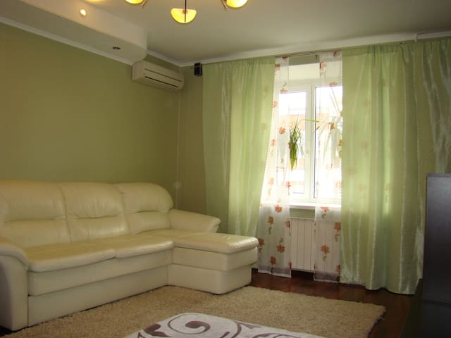 Living room with foldable sofa-bed, flat-screen TV and air-conditioning