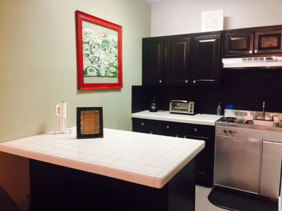 Kitchenette with dining bar, small refrigerator, Double stove top burners, and vintage poster of Atlanta