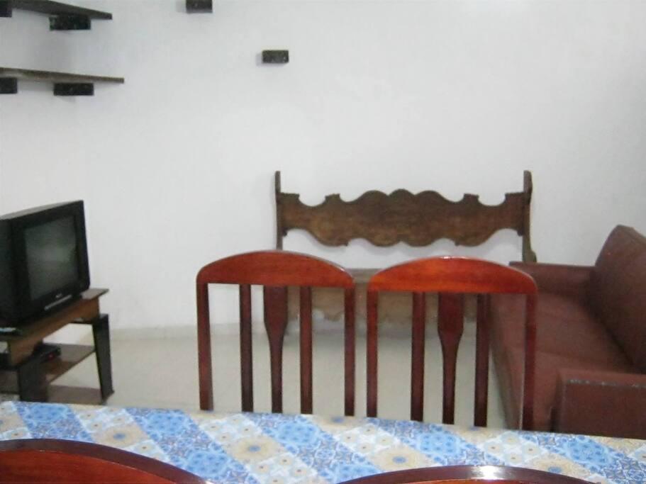 Sala com ventilador de teto, tv assinatura oi básica, cadeira para 6 pessoas, sofá para 3 pessoas e mesa para 6 pessoas.