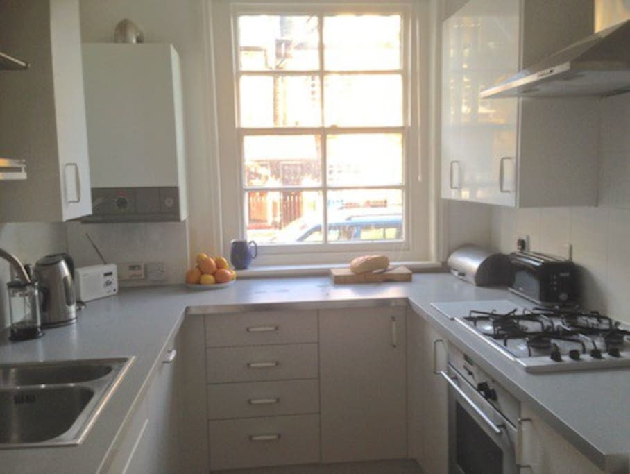 Well-equipped kitchen with gas hob, electric oven, dishwasher and washing machine.