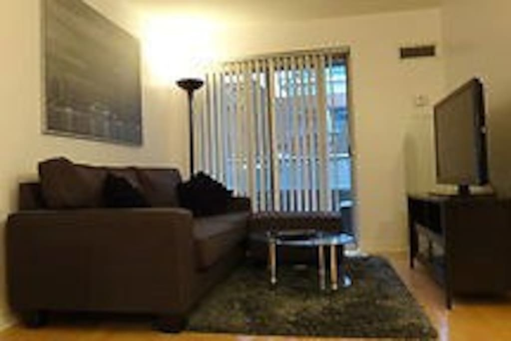 A cozy living room next to the carpeted balcony with a flat screen television giving you all the comforts of home