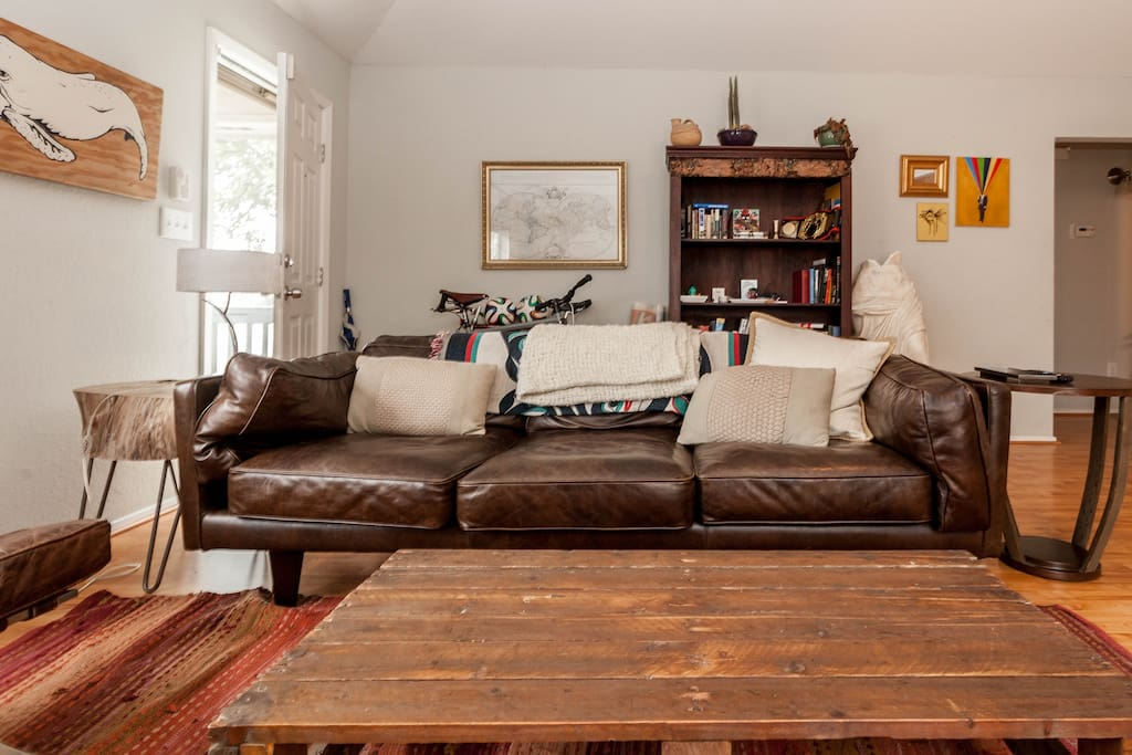 The living room has a leather couch, reclaimed wood coffee table, tree trunk side table, and original art.