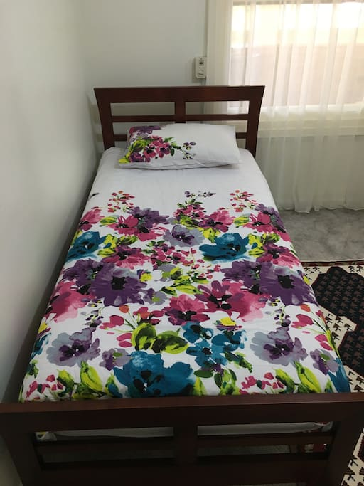 A brand new Wooden single bed with a comfortable almost new mattress and new beddings for your comfort.