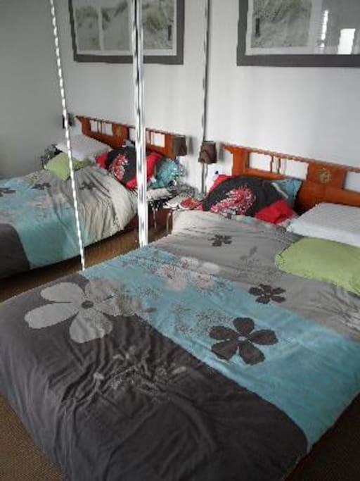 Chambre à coucher, à promixité de la salle de bains, qui possède une douche et une machine à laver.
