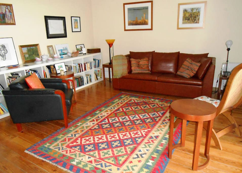 Another view of comfortable sitting room, showing sofa, easy chairs and bookcases.