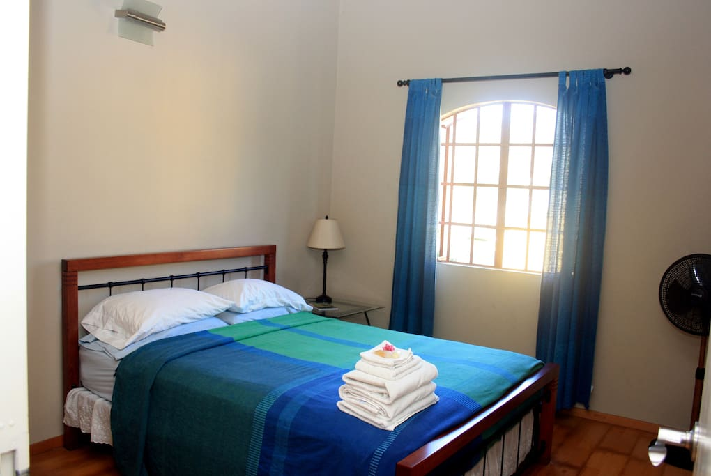Queen size bed with side table, lamp, air-conditioning, fan, cupboard space and lovely breezy view of the mountains.