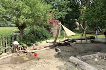 Natuurlijke waterspeelplaats met waterpomp en zandbak