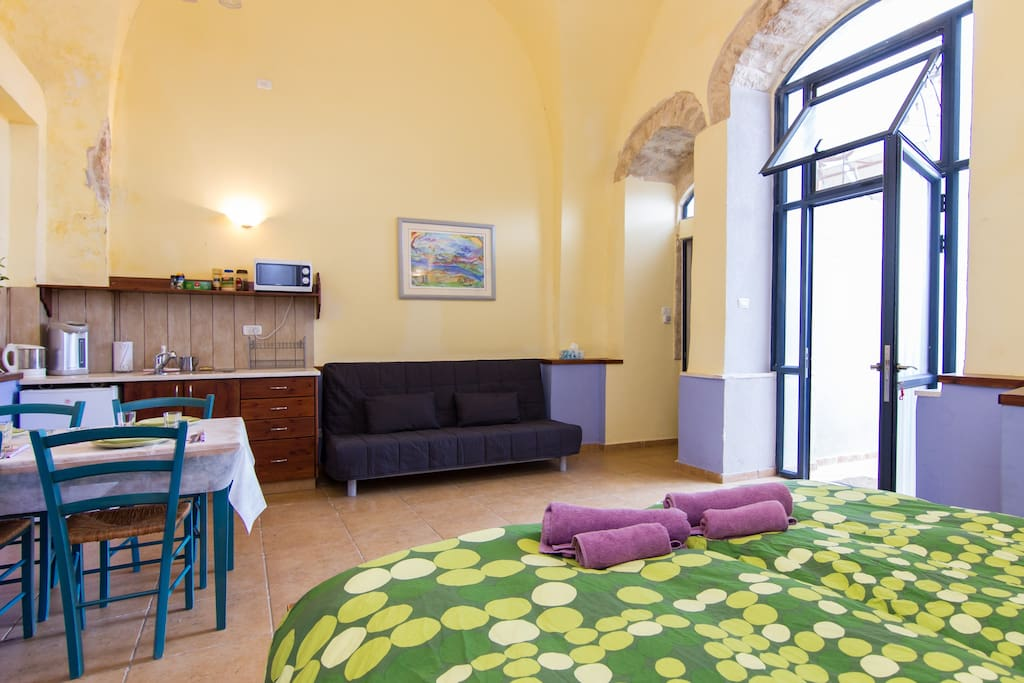 Plenty of air and light! Couch, beds, and quaint dining table.  Stone archways true to Old City Tzfat character.